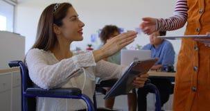 Młodzi żeńscy kierownictwa pracuje na cyfrowej pastylce w nowożytnym biurze 4k zdjęcie wideo