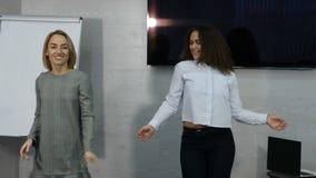 Młodzi żeńscy ludzie biznesu tanczyć szczęśliwy w biurze Szczęśliwy biznes drużyny odświętności zwycięstwo i taniec w biurze 4K zbiory