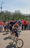 Młodzi aktorzy wykonuje w Gorky parku Kobiety i mężczyzna przejażdżki bicykle zdjęcia stock