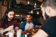 Młodzi arabscy mężczyzna ma śniadanie w kawiarni Najlepszy multiracial przyjaciele chłodzi out w barze zdjęcia stock