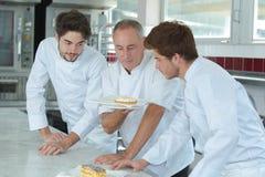 Młodzi asystenci i dojrzały szef kuchni patrzeje skończonego tort fotografia royalty free