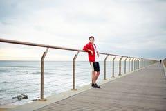 Młodzi atrakcyjni jogger stojaki na molu opiera na poręczu Obraz Royalty Free