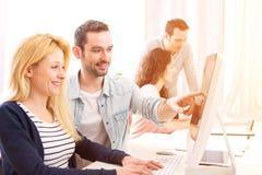 Młodzi atrakcyjni ludzie pracuje wpólnie przy biurem fotografia royalty free