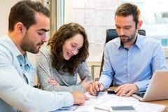 Młodzi atrakcyjni ludzie spotyka agenta nieruchomości przy biurem Zdjęcia Stock
