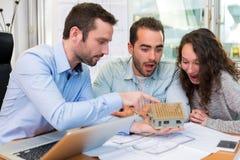 Młodzi atrakcyjni ludzie spotyka agenta nieruchomości przy biurem Obrazy Royalty Free