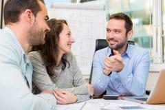 Młodzi atrakcyjni ludzie spotyka agenta nieruchomości przy biurem Obrazy Stock
