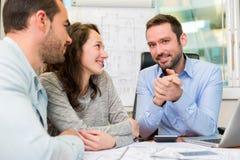 Młodzi atrakcyjni ludzie spotyka agenta nieruchomości przy biurem Fotografia Stock