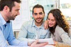 Młodzi atrakcyjni ludzie spotyka agenta nieruchomości przy biurem Zdjęcie Royalty Free
