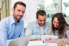 Młodzi atrakcyjni ludzie spotyka agenta nieruchomości przy biurem Fotografia Royalty Free