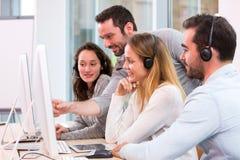 Młodzi atrakcyjni ludzie uczy się ich nową pracę przy centrum telefonicznym Zdjęcia Stock