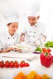 Młodzi attractives profesjonalistów szefowie kuchni gotuje wpólnie fotografia royalty free