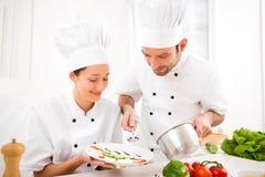 Młodzi attractives profesjonalistów szefowie kuchni gotuje wpólnie zdjęcia stock