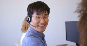 Młodzi Azjatyccy męscy klient sprzedaży kierownictwa opowiada na słuchawki w nowożytnym biurze 4k zbiory wideo