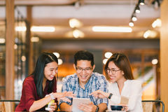 Młodzi Azjatyccy studenci collegu lub coworkers używa cyfrową pastylkę wpólnie przy sklep z kawą, różnorodna grupa Przypadkowy bi obraz royalty free