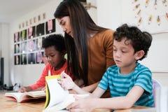 Młodzi azjatykci kobieta nauczyciela nauczania dzieciaki w dzieciniec sali lekcyjnej, preschool edukacji pojęcie zdjęcia royalty free