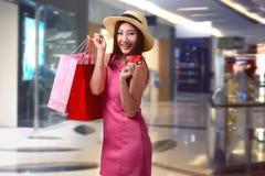Młodzi azjatykci kobiety mienia torba na zakupy i pokazują jej kredytową kartę Fotografia Royalty Free