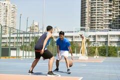 Młodzi azjatykci mężczyzna bawić się koszykówkę Obraz Stock