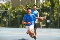 Młodzi azjatykci mężczyzna bawić się koszykówkę Obraz Royalty Free