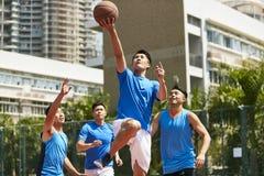 Młodzi azjatykci mężczyzna bawić się koszykówkę Fotografia Stock