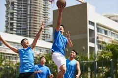 Młodzi azjatykci mężczyzna bawić się koszykówkę Zdjęcie Royalty Free