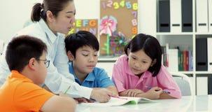 Młodzi azjatykci nauczyciel pomocy potomstw szkoły dzieciaki w klasie, zdjęcie wideo