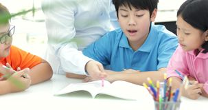Młodzi azjatykci nauczyciel pomocy potomstw szkoły dzieciaki w klasie, zbiory