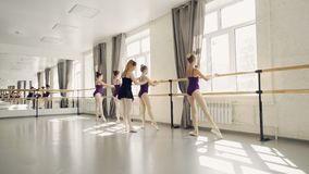Młodzi baletniczy tancerze ćwiczą nóg pozycje przy baleta barem pod przewodnictwem fachowej baleriny surowy nauczyciel zbiory wideo