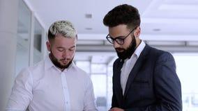Młodzi biznesowi koledzy patrzeje telefon dla coś zbiory wideo