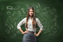 Młodzi bizneswomanów spojrzenia bezpośrednio przy uśmiechami na tle blackboard z kredowymi rysunkami i kamerą Fotografia Royalty Free