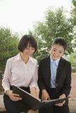 Młodzi bizneswomany pracuje outdoors patrzeć w dół w parku Zdjęcie Royalty Free