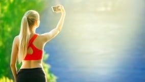 Młodzi blondynki kobiety stojaki na błękitnym dennym tle Sport kobieta w czerwonej koszulce robi selfie na naturze blisko morza Zdjęcia Stock
