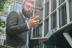 Młodzi brodaci biznesmenów stojaki przeciw nowożytnemu budynkowi, uses smartphone i chwytom, laptop w jego ręce Zdjęcie Royalty Free