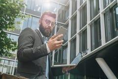 Młodzi brodaci biznesmenów stojaki przeciw nowożytnemu budynkowi, uses smartphone i chwytom, laptop w jego ręce Zdjęcia Royalty Free