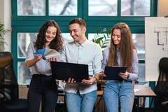 Młodzi caucasian architekci lub projektanci używa kolor paletę dla nowego projekta na laptopie w eleganckim nowożytnym biurze zdjęcia stock