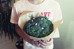 Młodzi chłopiec mienia brokuły w rękach Pojęcia zdrowy jedzenie zdjęcie stock