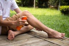 Młodzi chłopiec opryskiwania insekta repellents na jego nodze z kiści bott Zdjęcie Stock