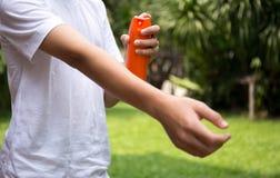 Młodzi chłopiec opryskiwania insekta repellents na skórze w ogródzie Obraz Stock