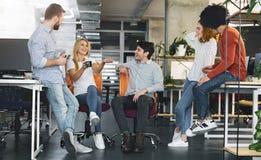 Młodzi coworkers ma przerwę w pracie, opowiada wpólnie i śmia się, fotografia royalty free