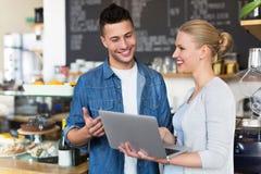 Młodzi cukierniani właściciele patrzeje laptop zdjęcia stock