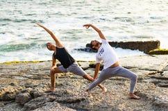 Młodzi człowiecy ćwiczą balansowych asanas na lata joga sesji na pięknej złotej plaży Lima, Peru - obraz stock