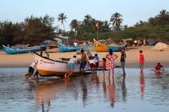 Młodzi człowiecy ciągnęli out łodzi rybackiej ashor Obrazy Royalty Free