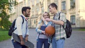 Młodzi człowiecy gawędzi i flirtuje z ładną blondynką blisko szkoły wyższa, ucznie zbiory
