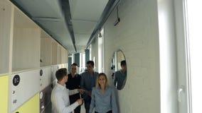 Młodzi człowiecy i kobiety chwalą each inny i ściskają odprowadzenie puszka korytarz biuro zbiory