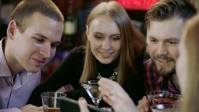 Młodzi człowiecy i kobiety ogląda przy telefonem komórkowym zbiory wideo