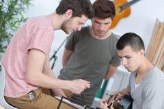 Młodzi człowiecy komponuje muzykę jeden bawić się gitara obrazy stock