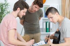Młodzi człowiecy komponuje muzykę w domu zdjęcia royalty free