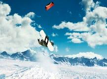 Młodzi człowiecy, przejażdżki jazda na snowboardzie na zamarzniętym jeziorze w górach w promieniach powstający słońce w zimie, Zdjęcie Royalty Free