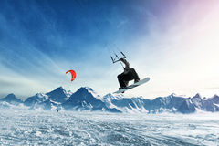 Młodzi człowiecy, przejażdżki jazda na snowboardzie na zamarzniętym jeziorze w górach w promieniach powstający słońce w zimie, Zdjęcie Stock