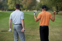 Młodzi człowiecy stoi w polu golfowym z kijami, tylni widok Fotografia Stock