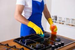 Młodzi Człowiecy w gumowym ochronnym cleaning i połysk kuchence czerń Fotografia Royalty Free